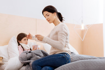 Thoughtful woman sitting with her ill child
