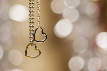 two hearts pendant necklace with glowing blurred background