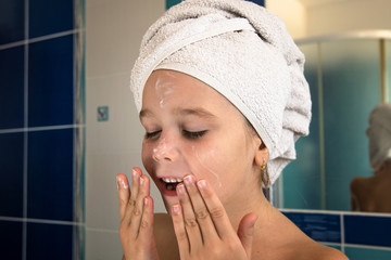 Little girl in bathroom with towel on a head and cream on face.