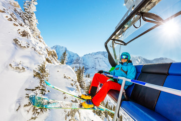 Skier sitting at ski lift in high mountains during sunny day
