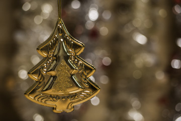 golden pine tree hanging on Christmas ornament with glowing blurred background