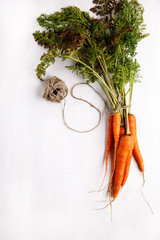 Bunch of fresh carrots with green leaves on white background.