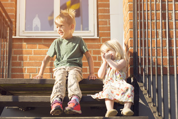 Boy (4-5) and girl (18-23 months) sitting on stairs outdoors
