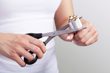 Concept of smoking control. Scissors in the hands. Scissors cut many cigarettes. Against smoking Health protection. On a gray background.