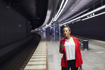 Woman in red coat waiting for train at station