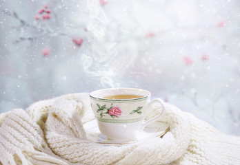 Hot tea in a beautiful white cup, wrapped in a knitted scarf amid a soft snow. Light gentle cozy cheerful winter christmas background.