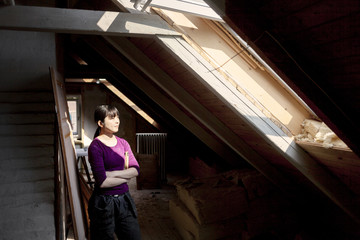 Woman in old attic looking at sunlight