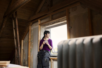 Woman during attic renovation resting by window