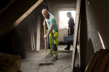Construction worker sweeping floor on attic under construction