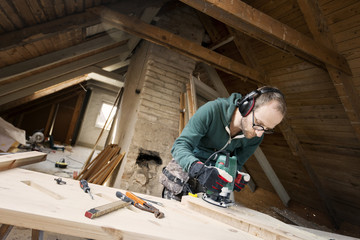 Man using power tool while renovating old attic