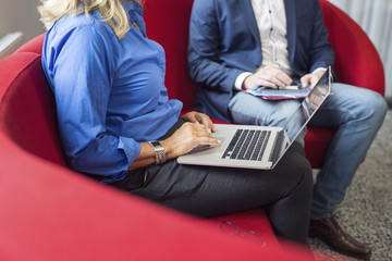 Two people sitting on red sofa with laptop