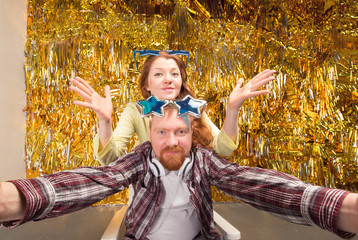 Selfie! Happy woman and man. Girl and boy with shaped stars glasses. Party, fun to spend time. Young woman holding camera and making selfie and smiling while standing against gold background