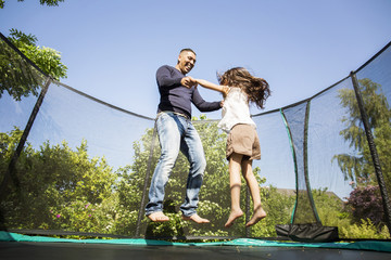 Girl (6-7) jumping on trampoline with father