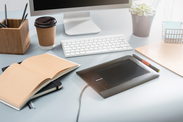 The gray desk with laptop, notepad with blank sheet, pot of flower, stylus and tablet for retouching