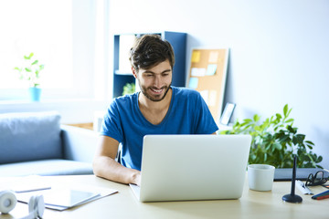Young man working on laptop in home office and smiling