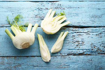 Ripe fennel bulbs on blue wooden table