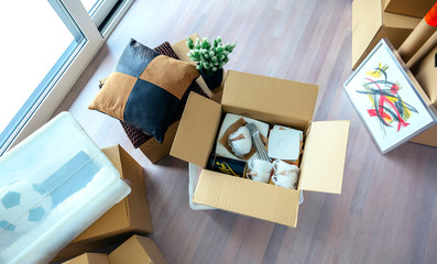 Large living room with stack of moving boxes and open kitchenware box