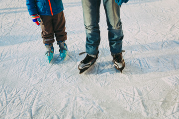 father with little son skating, family winter sport