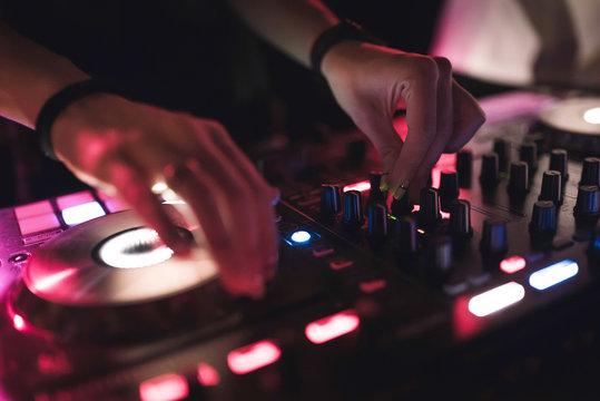 Hands of woman DJ tweak various track controls on dj's deck at night club
