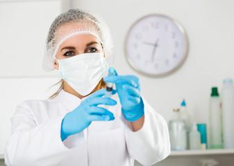 Female nurse preparing injection