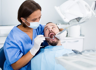 Dentist female in uniform is examinating of male in dental clinic