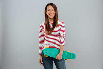 Happy asian woman in sweater holding skateboard
