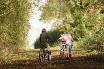 Boy and girl riding bikes in countryside