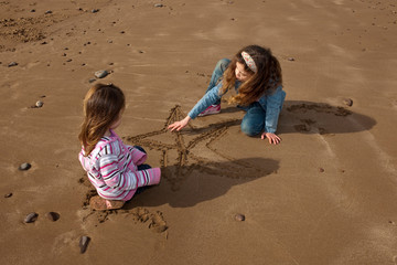 2 children drawing star on beach