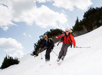 senior couple skiing in mountains