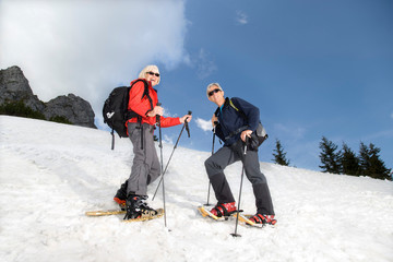 senior couple snowshoeing in mountains