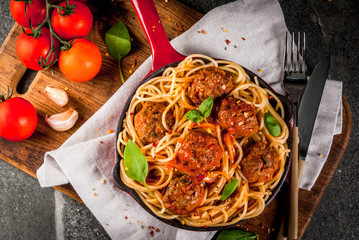 Spaghetti pasta with meatballs, basil tomato sauce in red cast iron pan, on black stone table with cutting board copy space top view