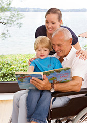 senior man reading book to boy