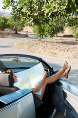 A woman reading a map in a car