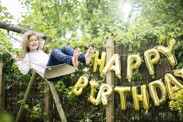 Portrait of swinging girl in garden with decoration for Birthday Party in the background