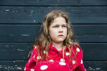 Girl wearing bathrobe outdoors sitting at wooden hut