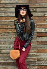 Beautiful brunette woman in sunglasses and in a hat  over wooden background Sends Air kiss. Street fashion. Outdoors.