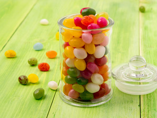 glass jar with lid filled with colorful candies on a wooden green background, many jelly bean scattered on the table