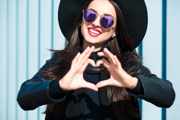 Happy young woman in glasses making a heart shape with her hands