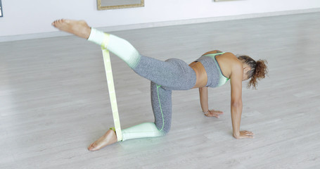 Fit young woman in sportswear posing on floor of studio using elastic band with stretch legs and all body before workout.