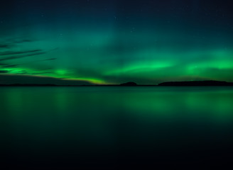 Northern lights dancing over calm lake. Farnebofjarden national park in Sweden.