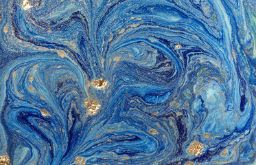 Marbled blue abstract background with golden sequins. Liquid marble ink pattern.