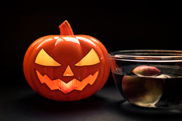 Halloween pumpkin head jack lantern and apple on water in glass bowl, black background. Halloween party and Apple bobbing concept.