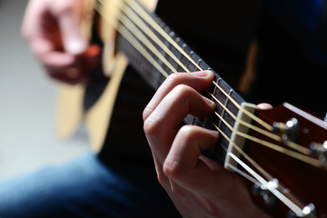 man's hands playing acoustic guitar, close up