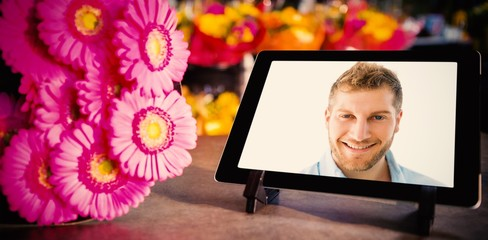 Composite image of digital tablet with pink flowers