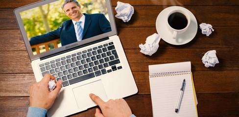 Composite image of confident businessman sitting on park bench