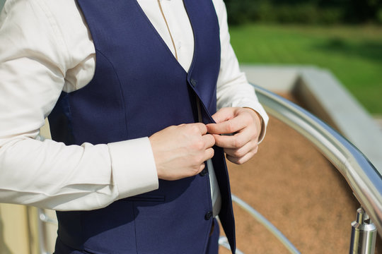 Young handsome man buttoning vest of blue suit. Getting ready for formal event concept. Horizontal color photography.