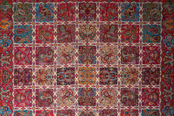 "Persian Handwoven Cloth ""Termeh"" With Teardrop Shaped Motifs, Paisley Pattern And Ornamental Designs and Colors Of Red, Green, Orange And Turquoise Blue. Top View Wallpaper Background"