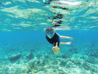 Woman snorkeling in clear sea water. Snorkel shows thumb in full face mask.