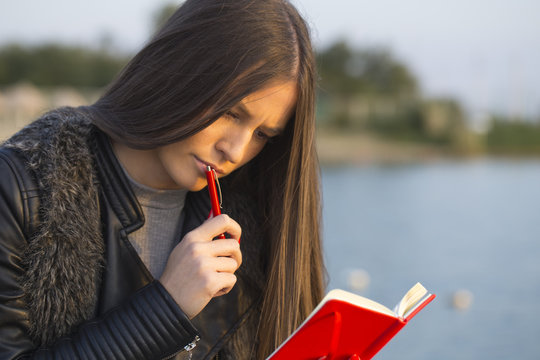 Portrait of a beautiful girl  while siting by the sea  and write in the notebook