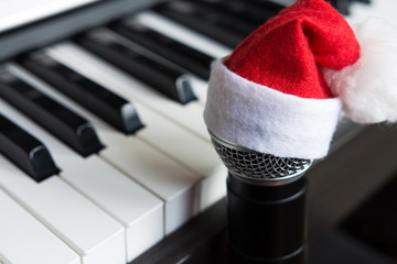 Microphone in Santa hat santa hat against piano keyboard background, concept of festive musical events selective focus, copy space